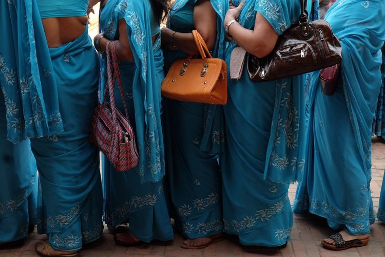 Low Section Of Women In Blue Sari Standing On Footpath