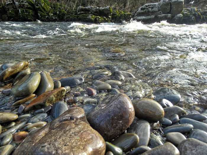 Riverside with rocks. Water Rock Solid Nature Stone Pebble Beauty In Nature Rock - Object Day Land No People Beach Stone - Object Outdoors Wet Flowing Water Shallow Flowing River Riverside Rocks Rock