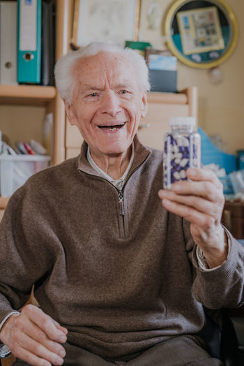 Portrait of smiling man holding camera at home