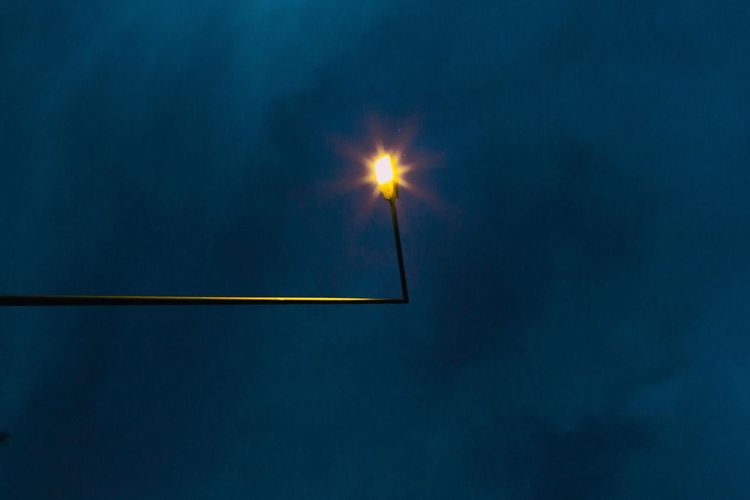 Low angle view of illuminated street light at night