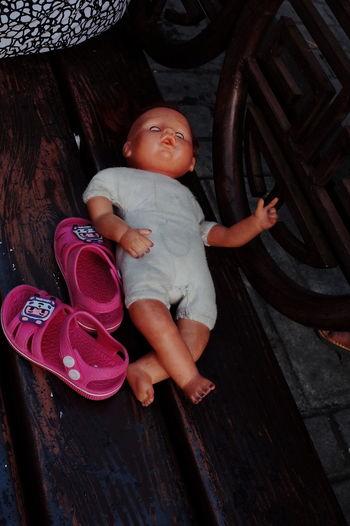 High angle view of cute baby girl lying on wood