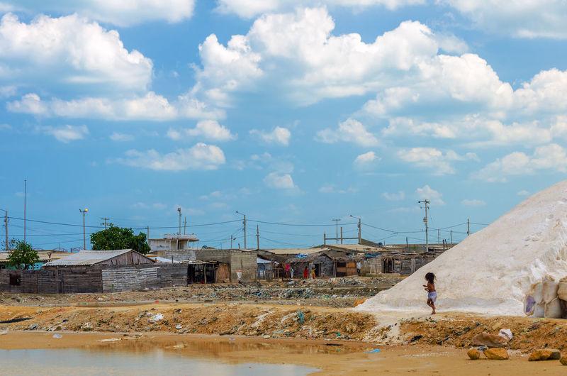Slat flat by slum against cloudy sky