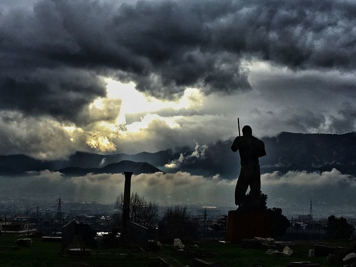 Silhouette of man standing on city against cloudy sky