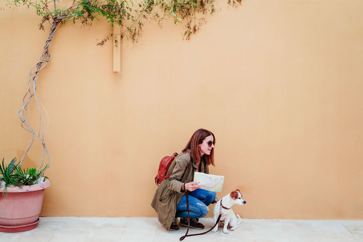 Woman crouching with dog by wall outdoors