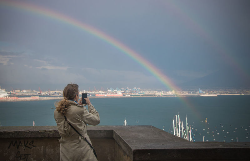Rear view of woman photographing double rainbow and lake