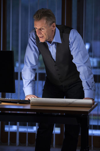 Senior architect or engineer standing at his desk looking at computer screen in a dark office