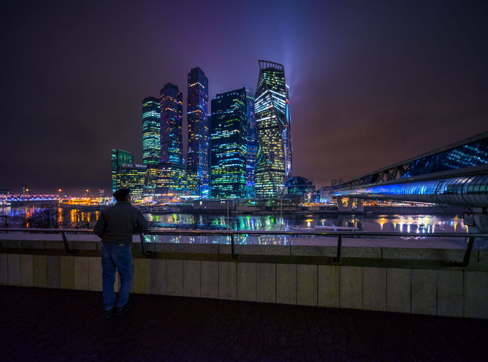 So close and yet so far: a man admires the skyscraper of the Moscow City financial district in the Russian capital on an overcast winter evening from the other side of the Moskva River Moscow City Architecture Business District City Cityscape Illuminated Lifestyles Night Office Building Exterior One Person Real People Skyscraper Standing