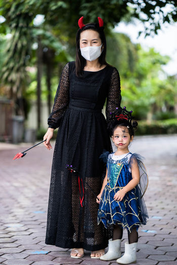 Mother and little girl in halloween costume standing outdoor