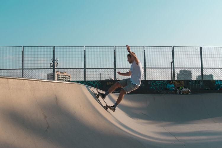 Side view of man skateboarding on skateboard against sky