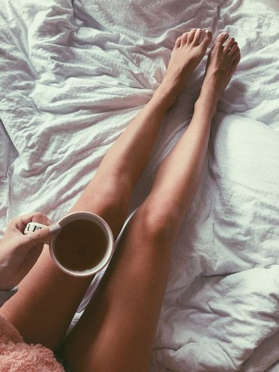 Low section of woman having coffee on bed