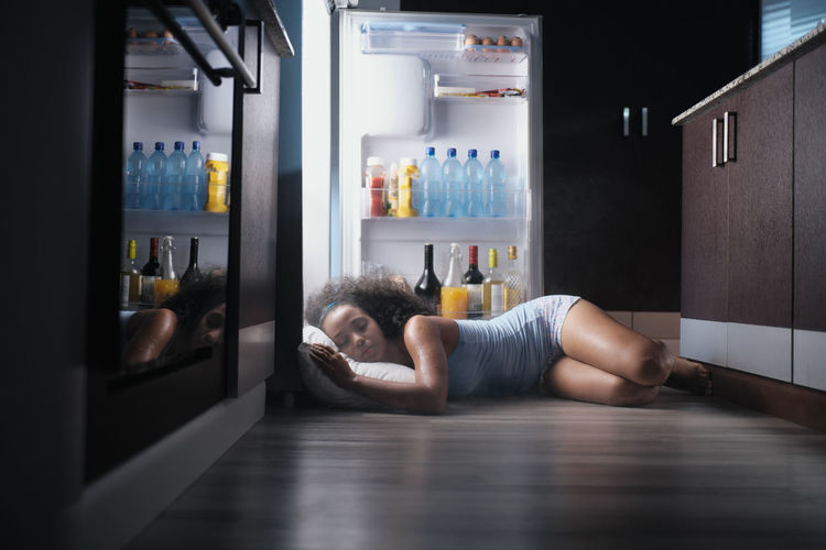 Portrait of shirtless man lying down in shelf at home