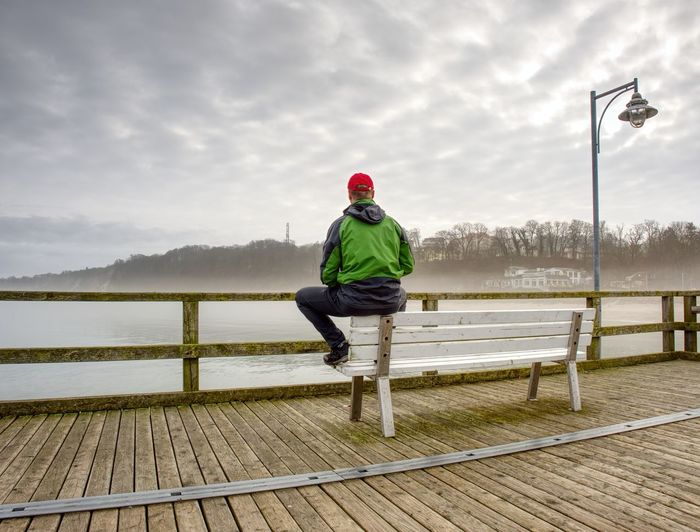 Rear view of man standing by railing against smooth baltic sea during rainy season