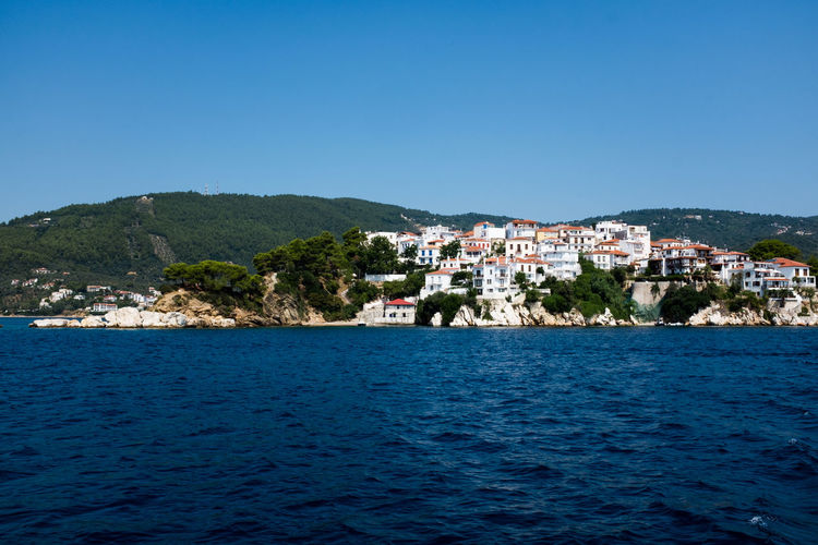 Scenic view of sea by town against clear blue sky