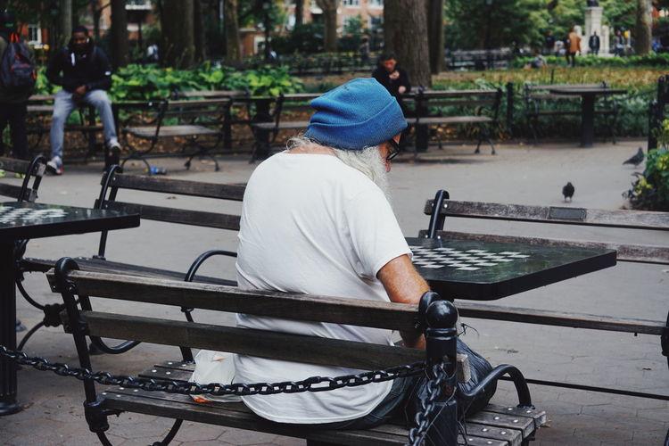 Rear View Of Senior Man Sitting On Bench At Park