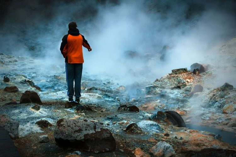 Man standing on rock formation by hot springs