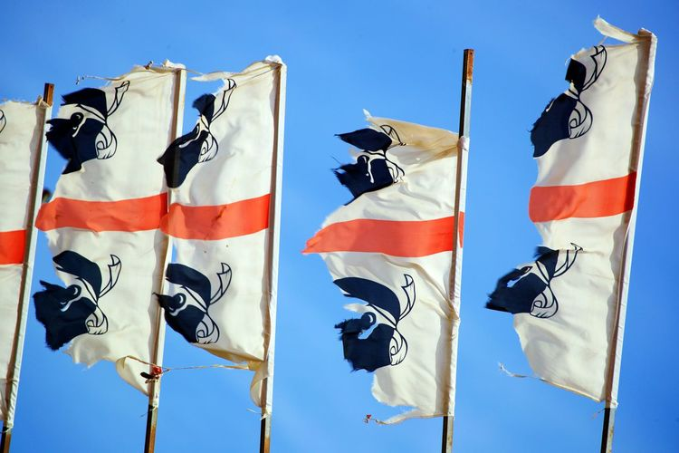 Low angle view of torn flags against blue clear sky