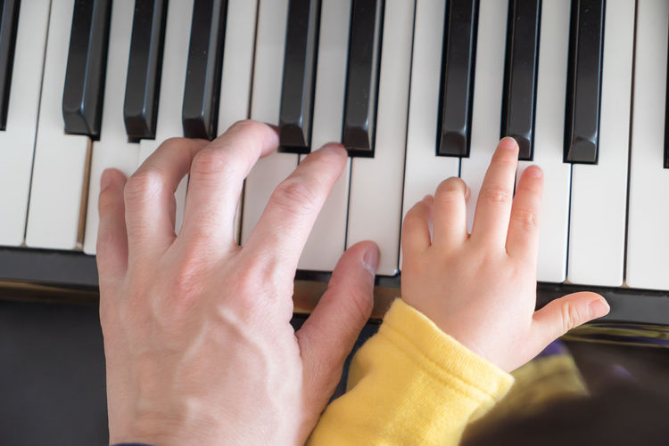 adult and a child's hand on a piano keyboard Human Hand Hand Musical Equipment Human Body Part Piano Musical Instrument Real People Music Arts Culture And Entertainment Finger Body Part Piano Key Indoors  Human Finger Playing Lifestyles Leisure Activity Keyboard Keyboard Instrument Man Family Cildren Parent