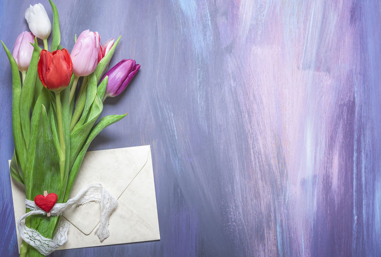 Close-up of tulips and envelop hanging on blackboard