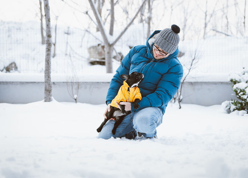 Winter Warm Clothing One Person One Man Only One Animal Smiling Pets Dog Domestic Animals French Bulldog Frenchbulldog Frenchie Puppy Purebred Dog Snow Covered Snow Bonding Cold Temperature Full Length Togetherness Friendship Men Winter Coat Deep Snow Canine