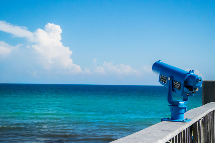Blue Coin-Operated Binoculars At Observation Point By Sea Against Sky