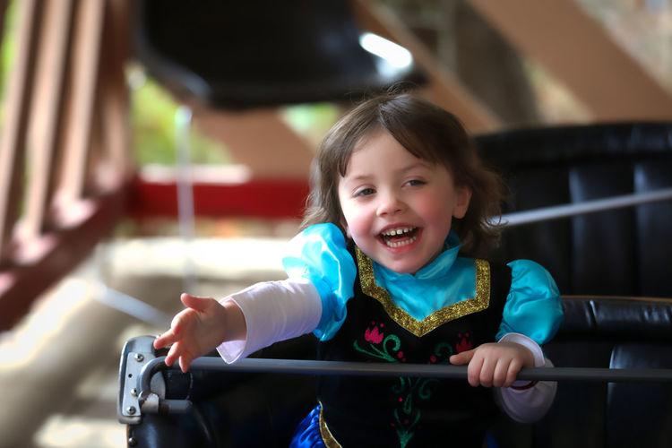 Smiling girl sitting in bumper car at amusement park