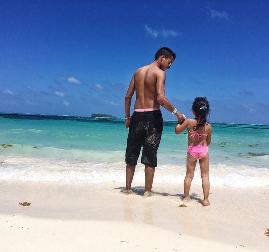 Rear View Of Shirtless Father With Daughter Standing On Shore At Beach