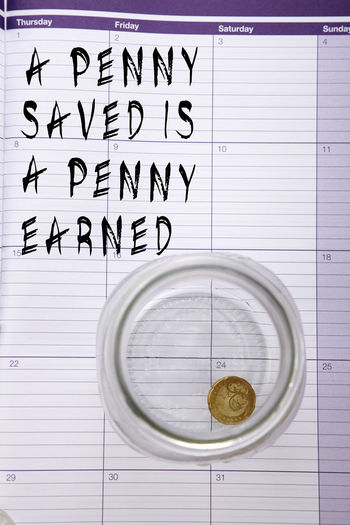 Directly above shot of text on diary with coin