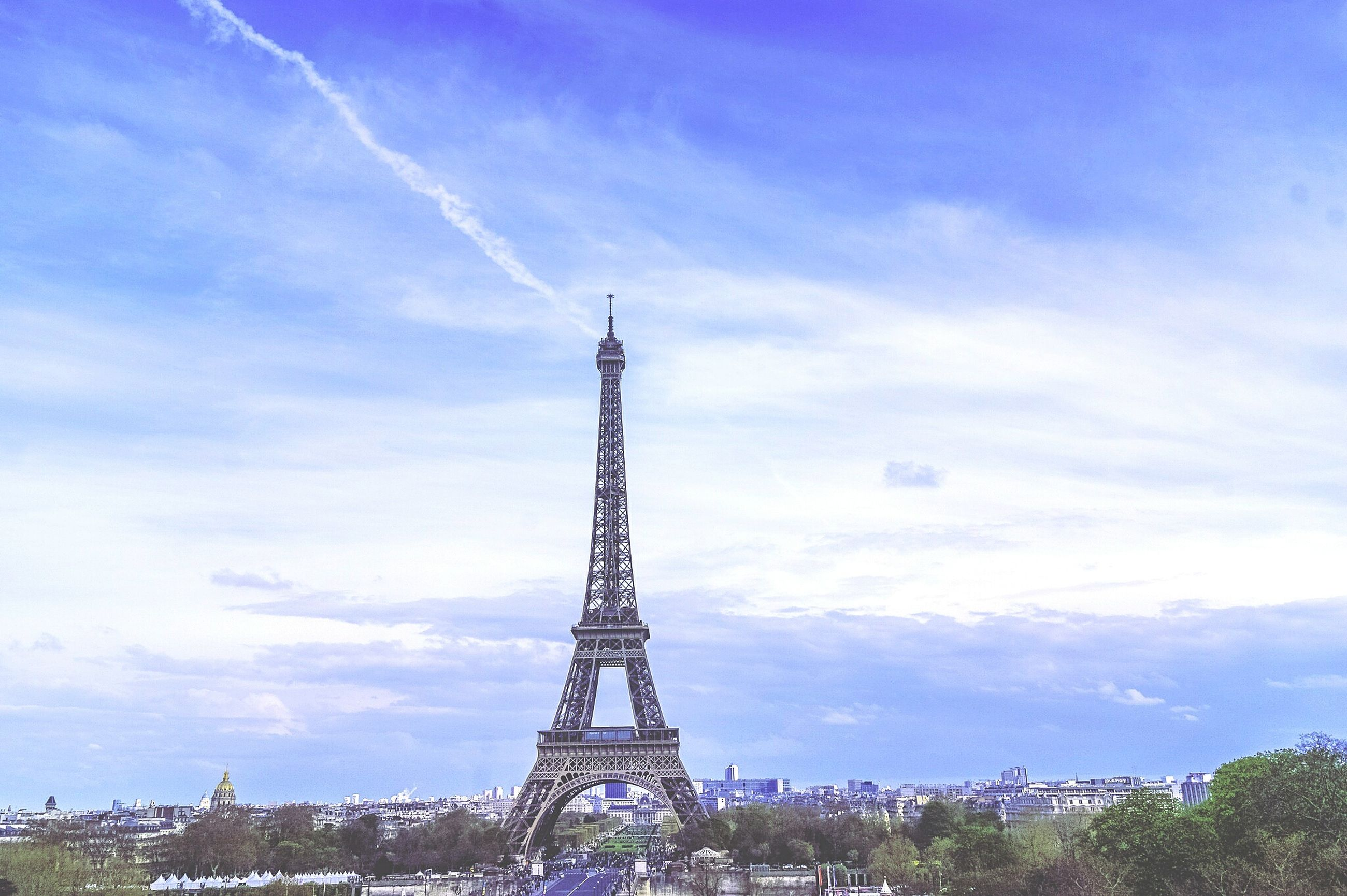 eiffel tower, built structure, tower, architecture, sky, tall - high, famous place, travel destinations, international landmark, low angle view, cloud - sky, tourism, communications tower, metal, capital cities, travel, culture, building exterior, tree, cloudy