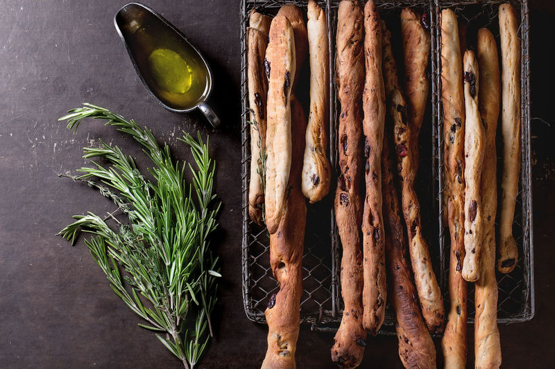 Fresh baked homemade grissini bread sticks in vintage metal grid box with olive oil and herbs rosemary and thym over dark surface. Top view. Apetizer Bread Dark Background Food Healthy Eating Herbs Homemade Italian Food Meal Mediterranean Food Olive Oil Rosemary Herb Snack Top View Of Food Traditional