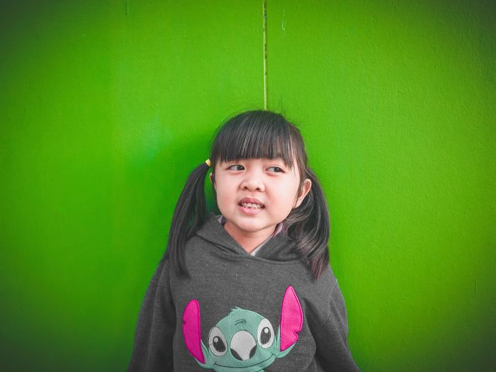 Smiling girl looking away while standing against green wall
