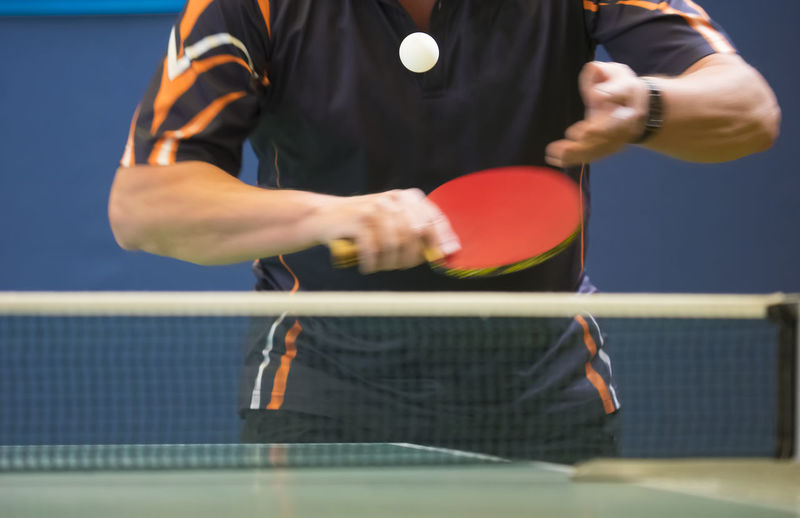 Table Tennis Player serving, motion blur, focus at the ball Ball Competition Front View Holding Leisure Activity Men Midsection Motion Net - Sports Equipment One Person Playing Racket Real People Skill  Sport Standing Table Tennis Tennis Tennis Net