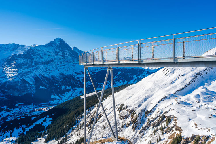 Bridge over snowcapped mountains against sky