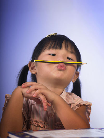 Close-up of cute girl playing with pencil at table against wall