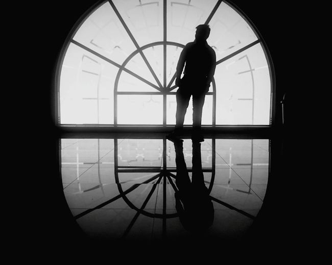 Silhouette man standing against clock