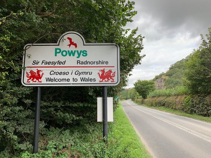 Information sign by road against sky