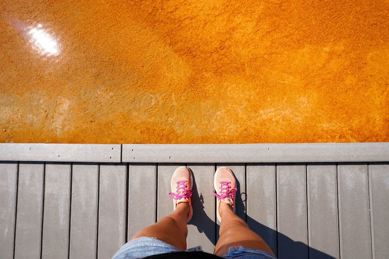 Low Section Of Woman Standing On Jetty By Orange Water