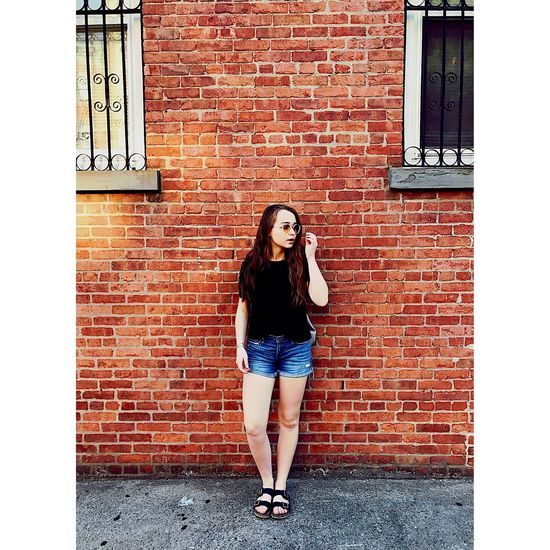 Brick Wall Only Women Communication One Person Young Adult Full Length Leaning One Young Woman Only One Woman Only Wireless Technology Long Hair Smart Phone Standing Front View Technology Day Adult Young Women Outdoors Adults Only