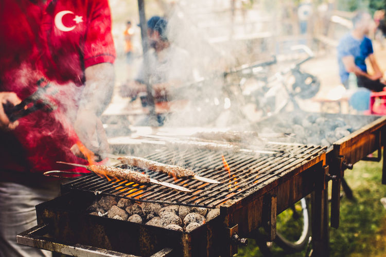 Midsection of man preparing barbecue on grill at market