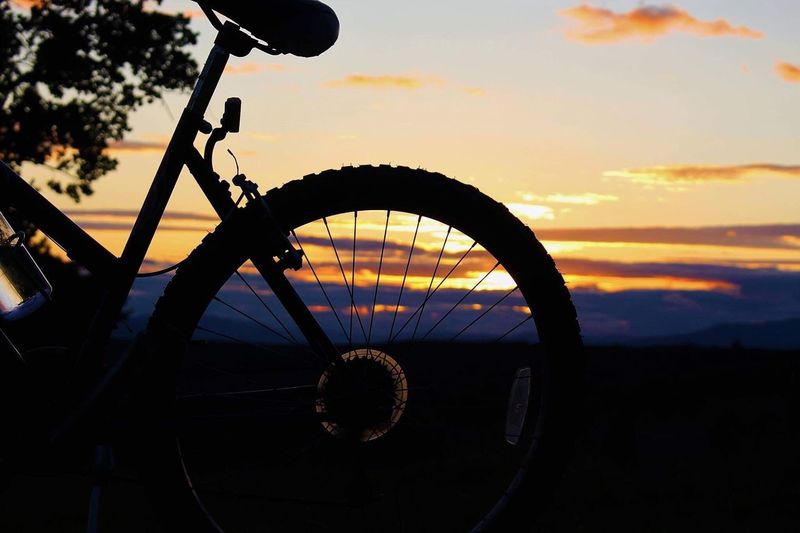 Close-up of bicycle wheel against sky during sunset