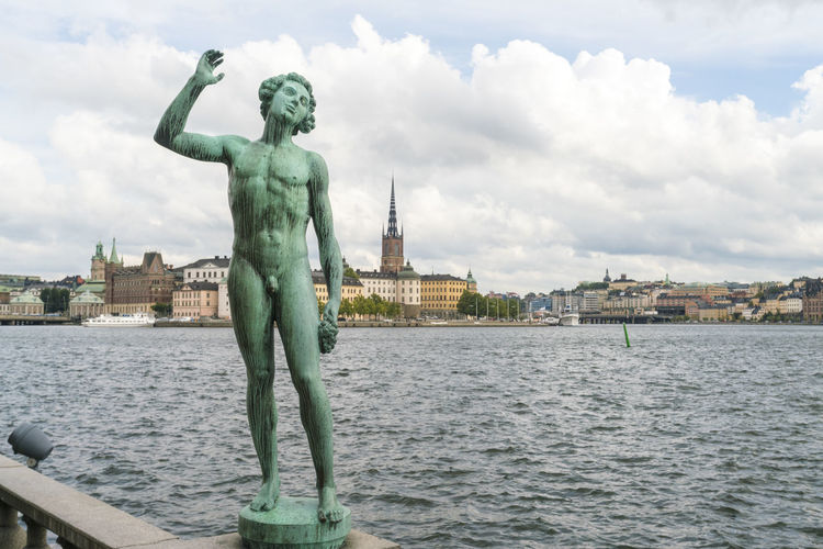 Statue of river with city in background