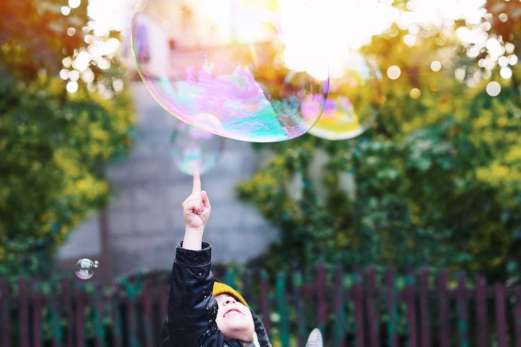 Girl Playing With Bubble In Yard