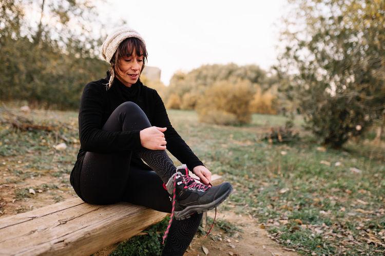 Full length of woman sitting on land