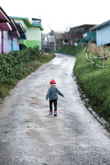 Rear view of toddler running on single lane road in village