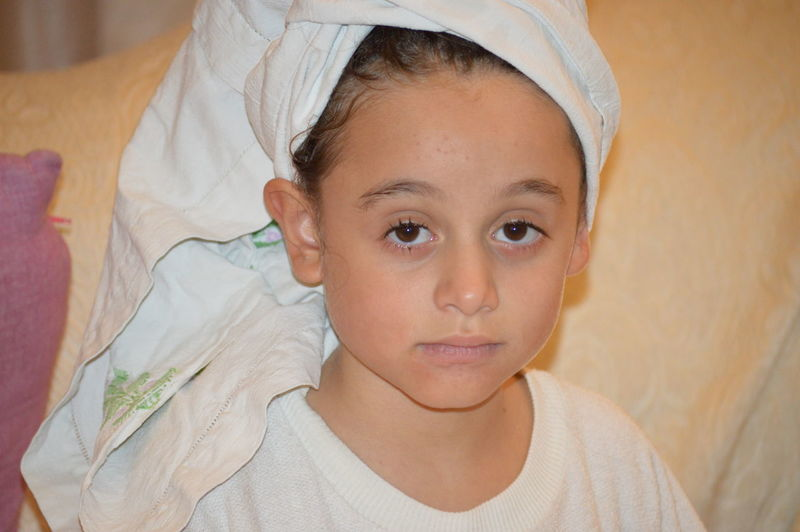 Close-Up Portrait Of Cute Girl Wrapped In Towel At Home