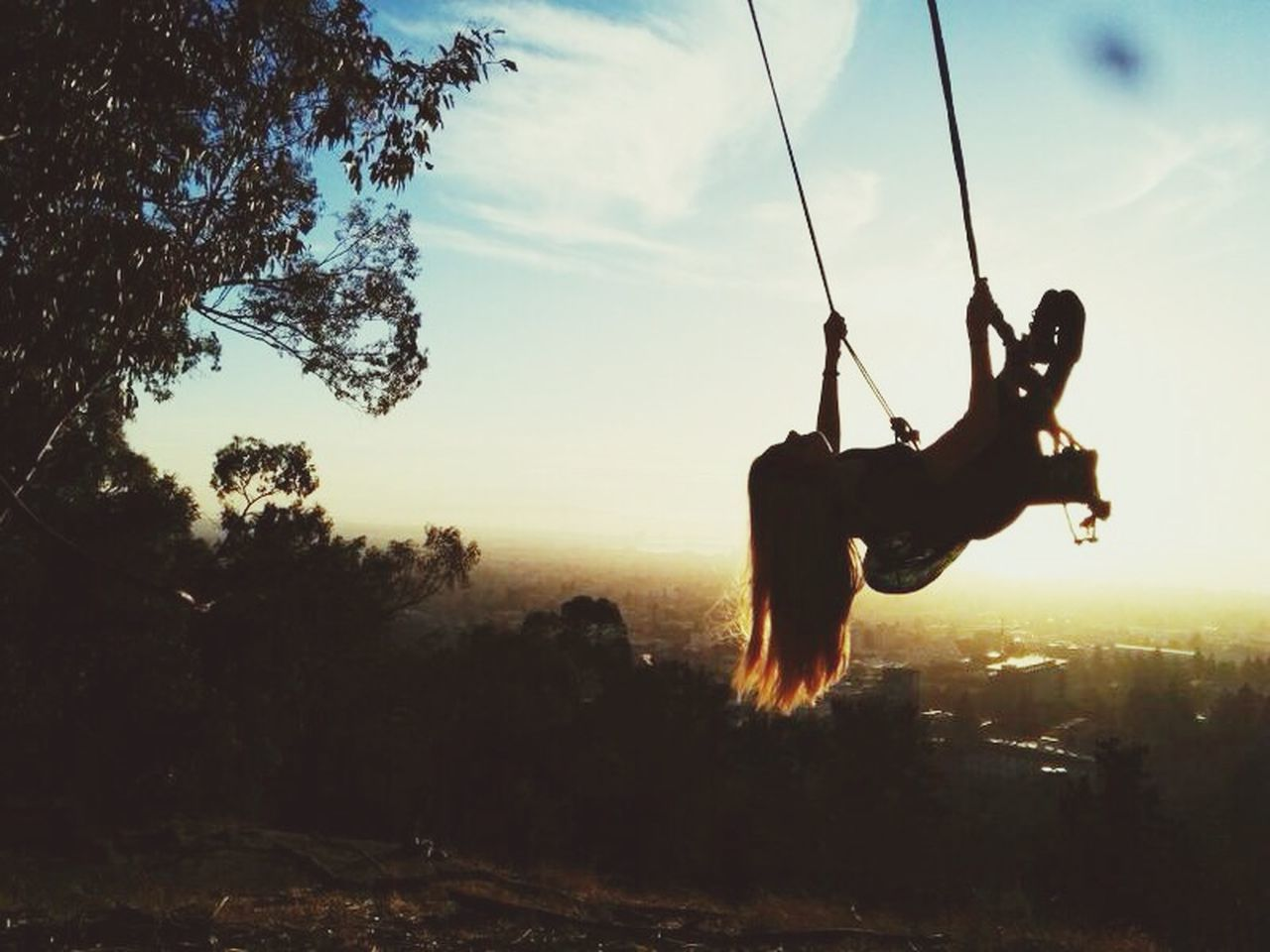 Low angle view of girls swinging in park during sunset