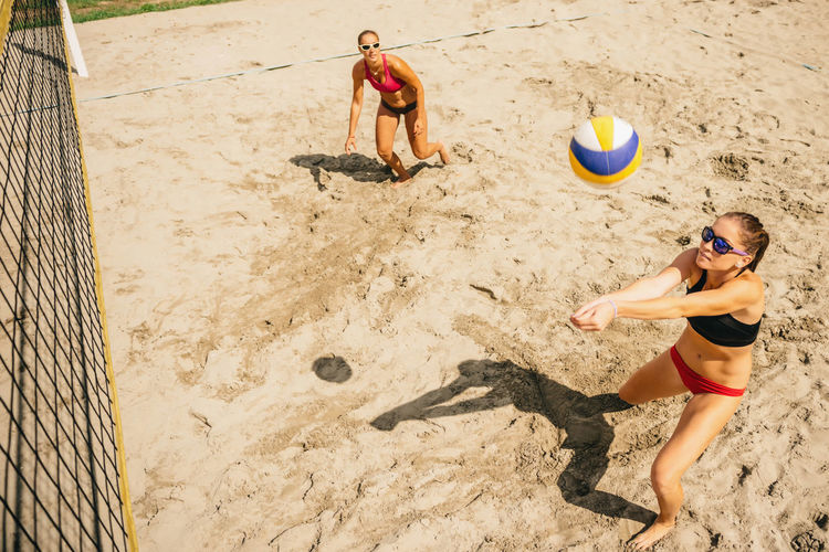 High angle view of friends playing volleyball at beach
