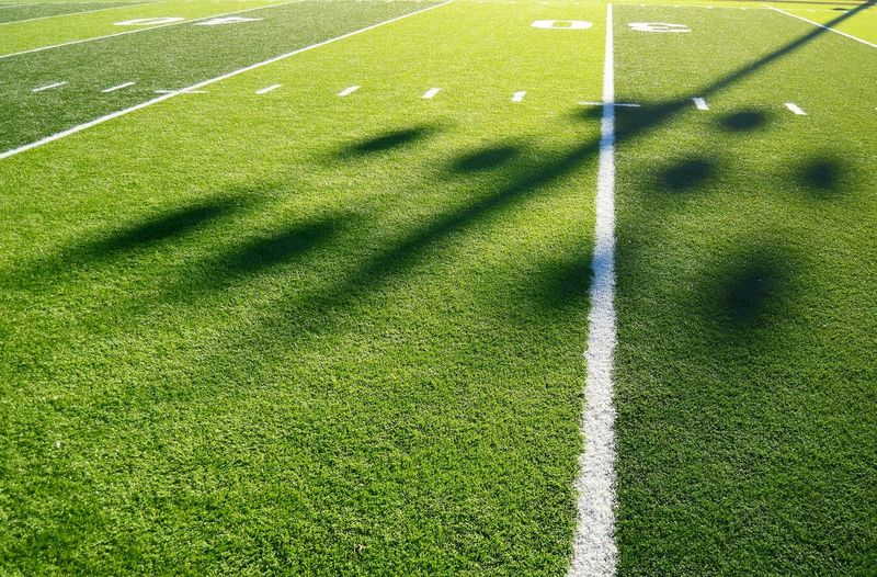 Long afternoon shadows on american football field