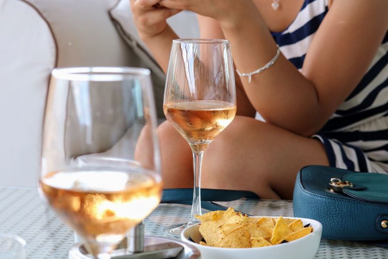 Midsection of woman with food and drink on table