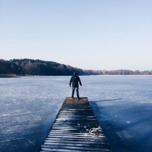Full length rear view of man standing on pier over lake