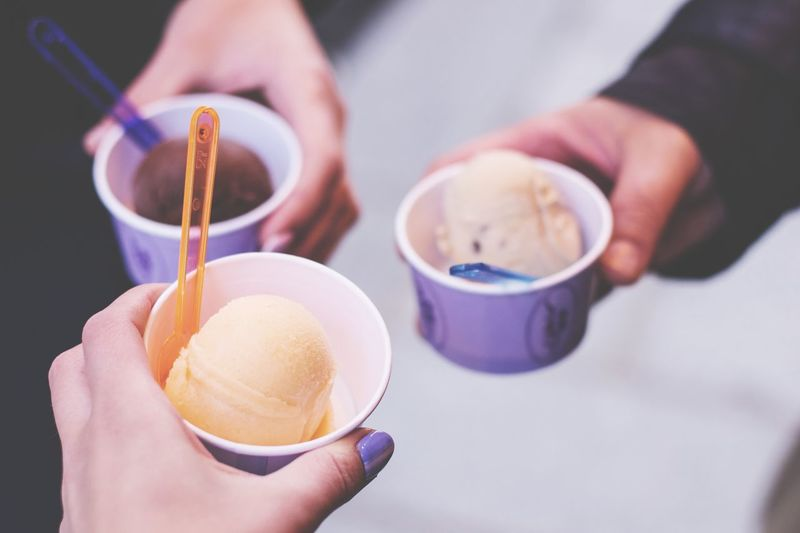 Close-Up Of Hand Holding Ice Creams In Containers On Footpath